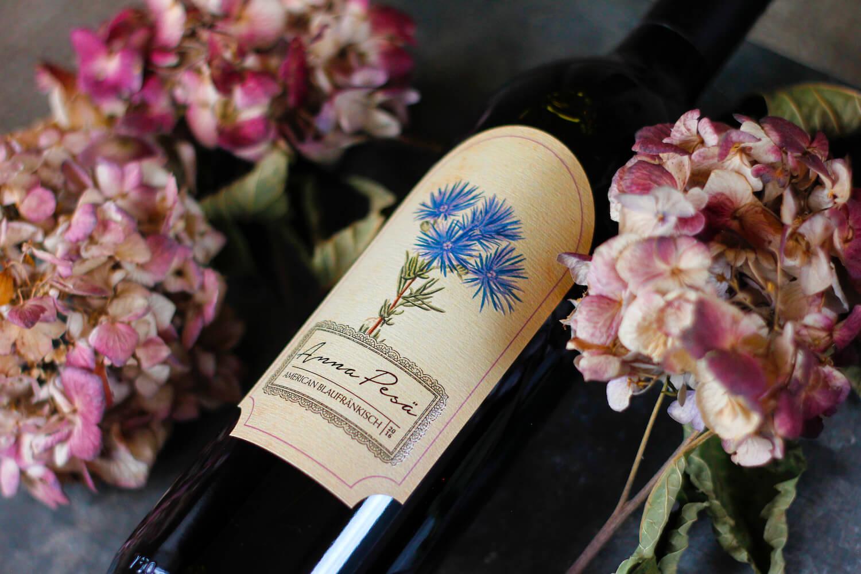 A bottle of Anna Pesä Blaufränkisch wine in a bed of flowers