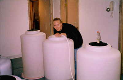 Winemaker Sandi posing with Prairie Berry Winery's first commercial fermentation tanks in Mobridge, South Dakota